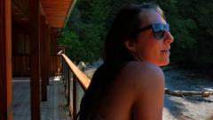 4K Young Woman Enjoying Cabin Deck overlooking Pacific Coastal Beach and Ocean - stock footage