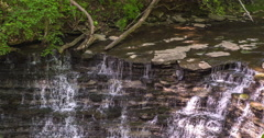 Waterfall going down rock face in woods 4k Stock Footage