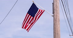 American Flag blowing in wind off telephone pole 4k Stock Footage