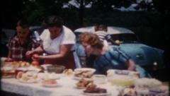 2239 - women set tables with food for big family picnic -vintage film home movie Stock Footage