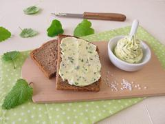 Sliced bread with herb butter - stock photo