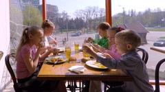 five children between five and ten years old dine in the restaurant - stock footage