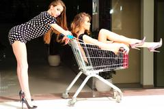 Sexual women with shopping trolley - stock photo