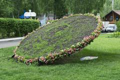Topiary figure - sundial in the form of inclined wheel - stock photo