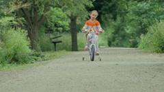 Beautiful girl riding bike in the park Stock Footage