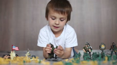Cute little toddler boy, playing at home with soldiers and figurine toys, pla Stock Footage