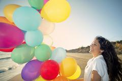 Happy woman with multi colored balloons - stock photo