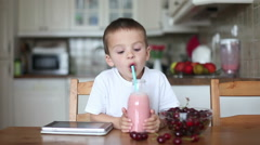 Happy school boy drinking  healthy smoothie as a snack at home, eating cherri Stock Footage