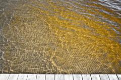 Yellow ocean water discolored by clean sediments - stock photo