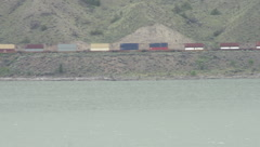 Railroad, container train on lake shore long lens, on the other side of the lake Stock Footage