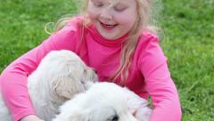 Beautiful little girl playing with the puppies in nature - stock footage