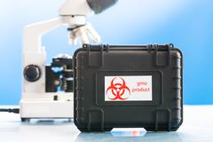 Safe case with GMO product and microscope in laboratory Stock Photos