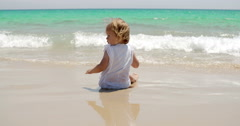 Little girl romping at the edge of the surf Stock Footage