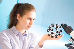 Young woman scientist working at the laboratory. Model of molecule in hand Kuvituskuvat
