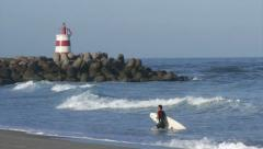 Tavira Island Inlet Lighthouse and surfer leaving water Stock Footage