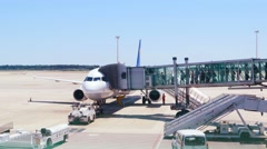 Passengers boarding airplane in airport, another plain taking off on background. Stock Footage