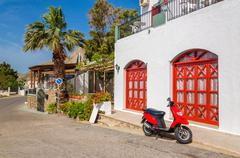Red motorbike in front of typical Greek house Stock Photos