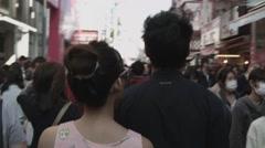 A teen couple walk through Takeshita Street Stock Footage