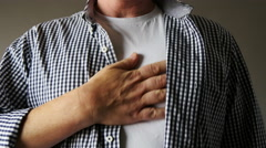 Man with heartburn rubs chest Stock Footage