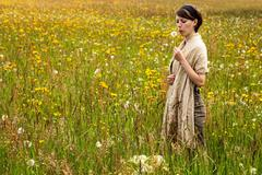 Young woman with a dandelion in a colorful wildflower meadow - stock photo