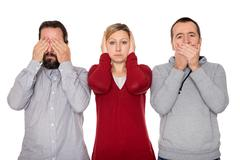 two men and a woman shows three wise Monkeys - stock photo
