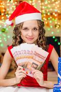 The girl is holding a Christmas gift certificates Stock Photos