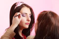 Makeup artist stylist applying eyeshadow on eyelid of woman Stock Photos