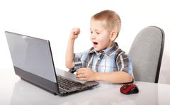 Stock Photo of Computer addiction emotional boy with laptop