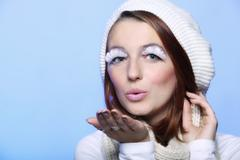 Winter fashion girl warm clothing creative makeup blowing kiss Stock Photos
