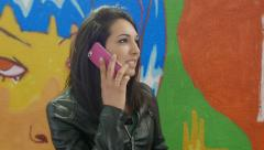 Young woman talking at the mobile phone near  murals Stock Footage