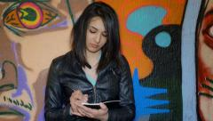 Young student taking notes near a murals Stock Footage
