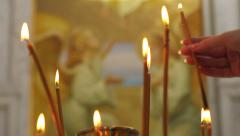 Woman's hand sets a candle into a candlestick. - stock footage