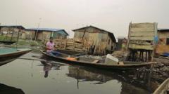 Man Paddling a Canoe along a dirty canal in Makoko Lagos Nigeria Stock Footage