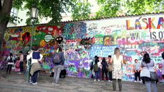 People near the Lennon Wall: tourist visiting Prague Stock Footage