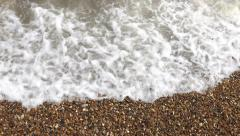 High Angle Shot of Ocean Waves Washing Up on to a Pebbled Beach - stock footage