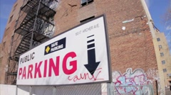Parking sign with arrow and graffiti red brick building Queens parking lot NYC Stock Footage