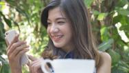 Stock Video Footage of Young Asian girl using smartphone in the garden cafe