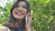 Stock Video Footage of Young Asian girl using smartphone in the garden