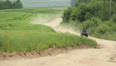 ATV riding on rural road picking up a lot of dust Stock Footage