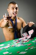 Stock Photo of Man drinking and playing in casino