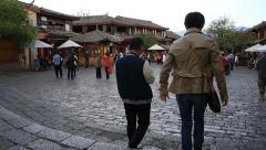 Couple walking into the main square of Lijiang old town Stock Footage