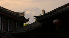 Jade dragon snow mountain seen from Lijiang old town at sunset Stock Footage