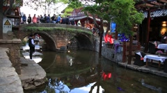 Tourists taking photos on the stone bridge of Lijiang old town in China Stock Footage
