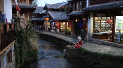 Woman in traditional cloth taking photos in old town of Lijiang Stock Footage