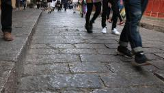 Tourists walking on traditional stone street in old town of Lijiang Stock Footage
