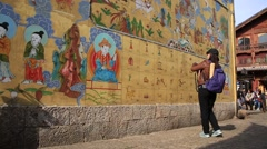 Woman taking photos of the wall painted with The Dongba symbols Stock Footage