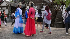 Women in traditional costumes around famous watermill in Dayan old town, Lijiang Stock Footage