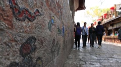 People walking by the wall painted with The Dongba symbols Stock Footage