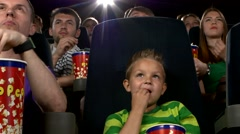 Little boy eating popcorn and watching movie at the cinema - stock footage