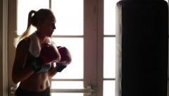 Young Woman Boxer Punches Training Bag in Silhouette Stock Footage